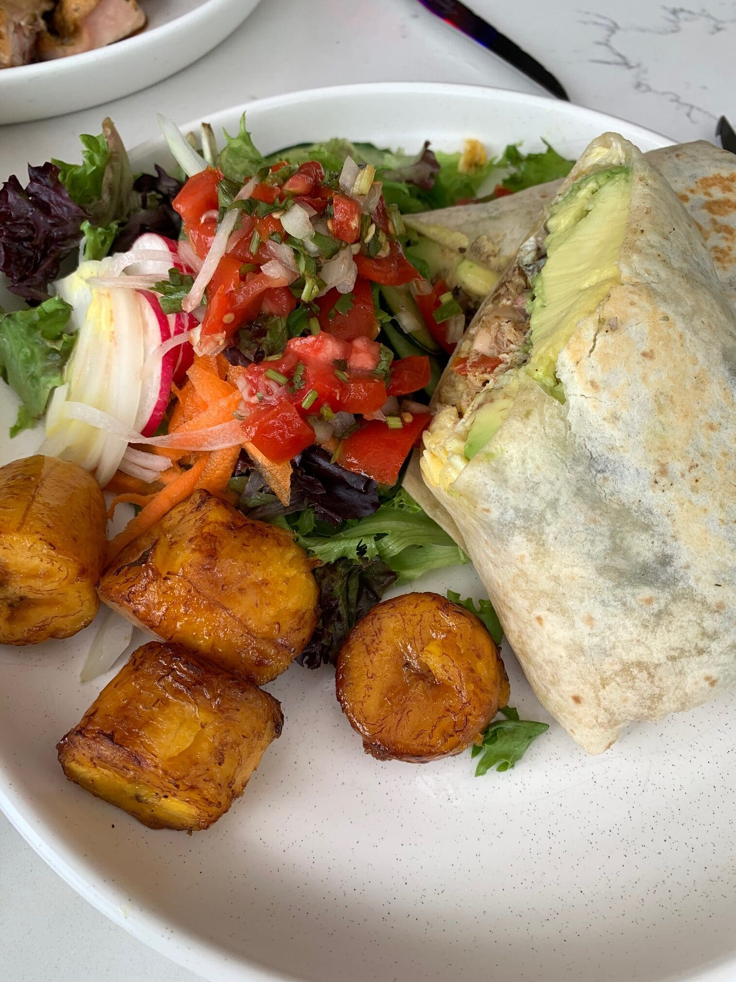 Tortilla roll filled with chicken, side of plantains and salad
