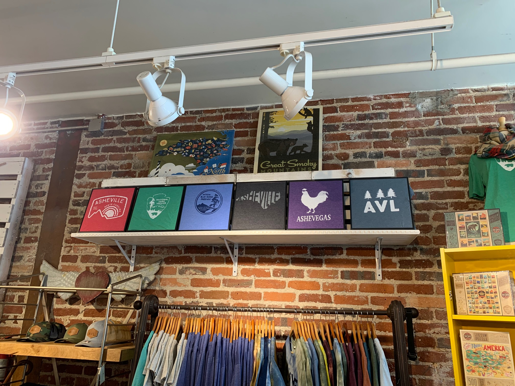 brick wall with Asheville t-shirts at Duncan & York