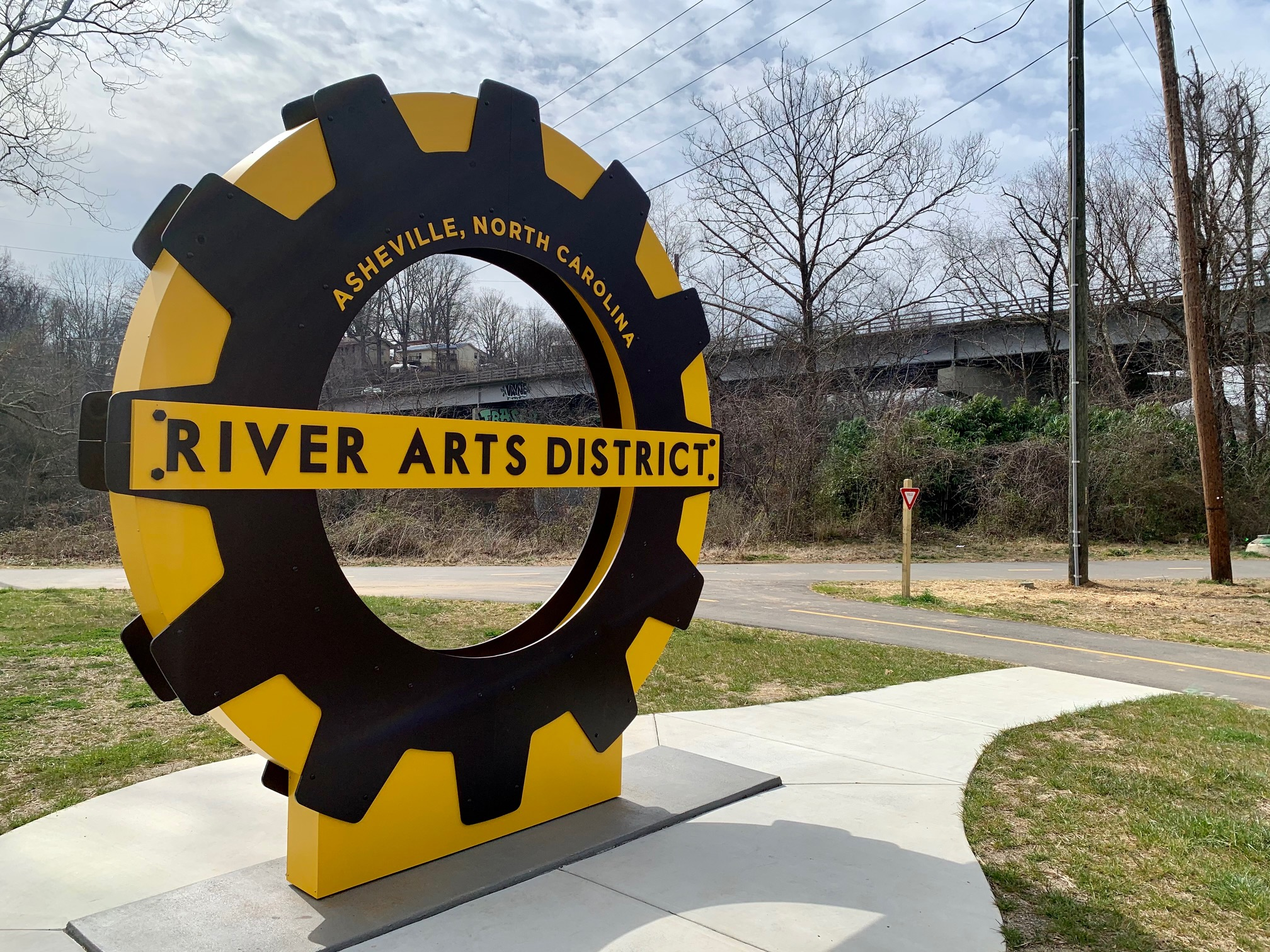 Yellow black sculpture sign that says River Arts District