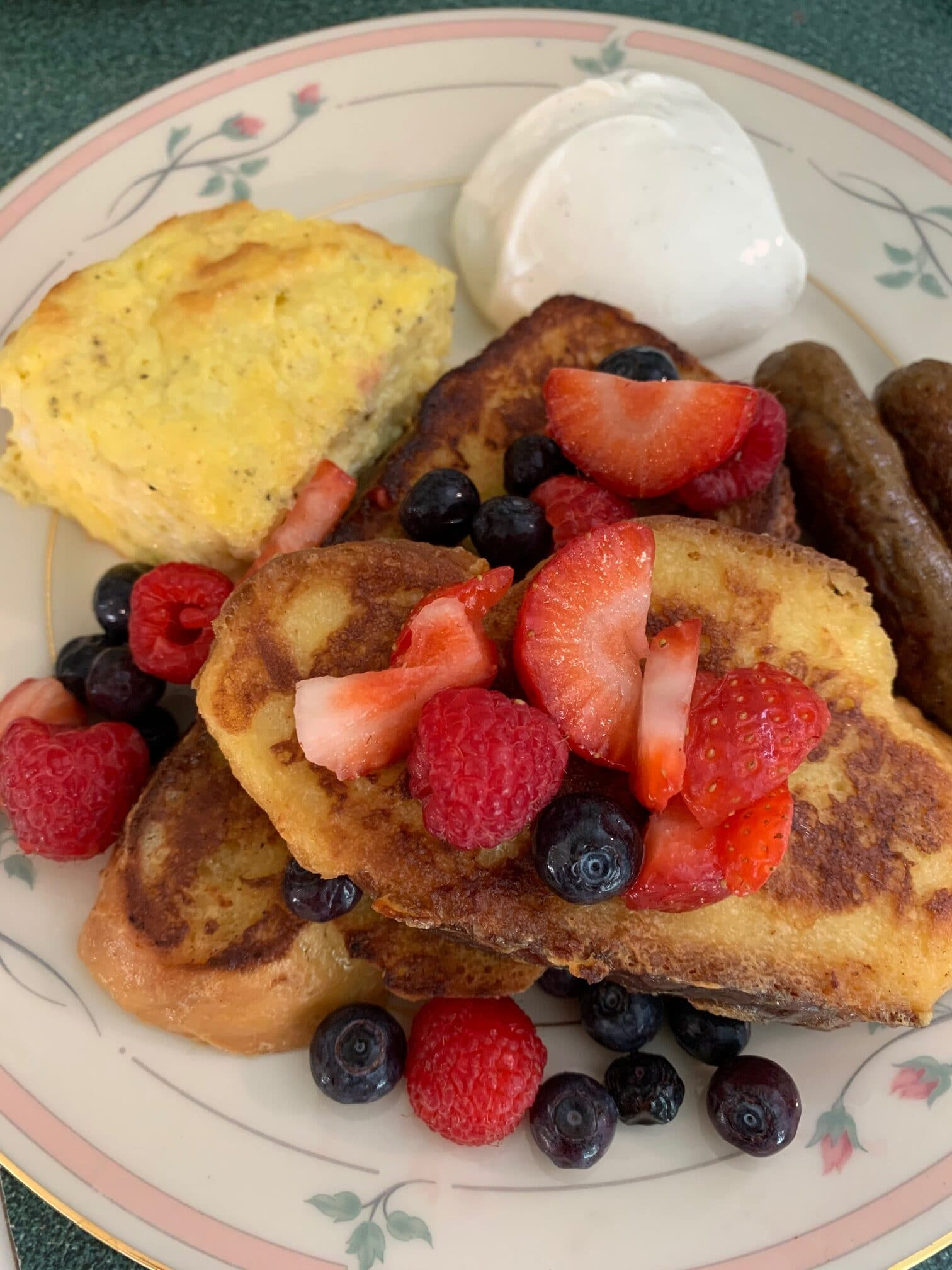 a plate of breakfast food like eggs, french toast, and yogurt with berries