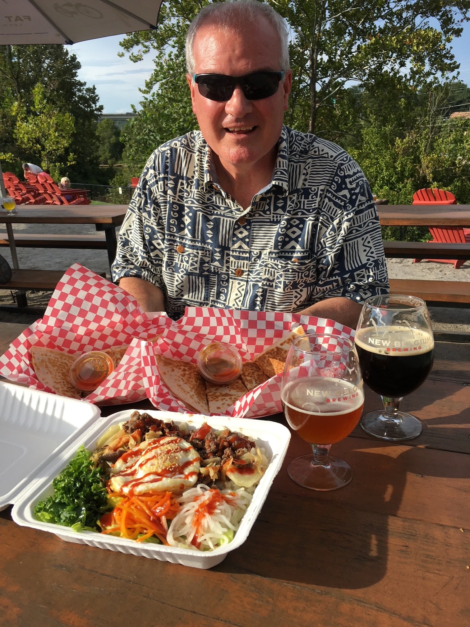Man at picnic table with beer and Korean food